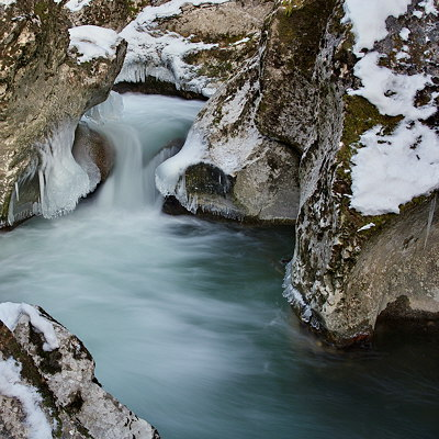 Photo of a cold little waterfall running between rocks and ice in Fornant river