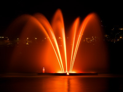 Photograph of a colorful illuminated fountain on Annecy lake by a winter night