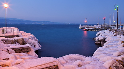 Photo of Geneva lake at blue hour in winter with the banks covered with ice