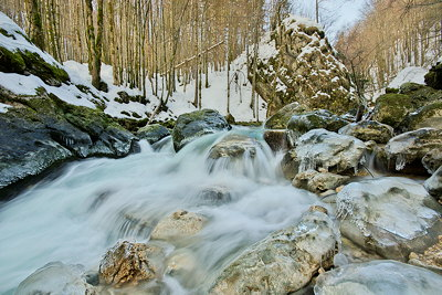 Photo of Valserine river in winter with ice on the banks